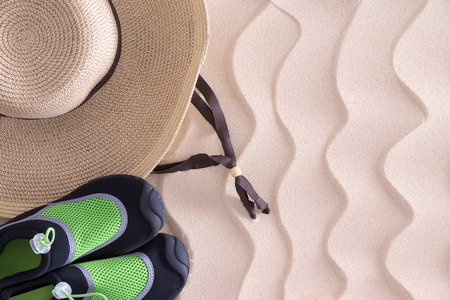 swim shoes: Overhead view of a young boys straw sunhat and green casual shoes on golden sand with a decorative wavy pattern and copyspace on a tropical beach left behind when he went to swim