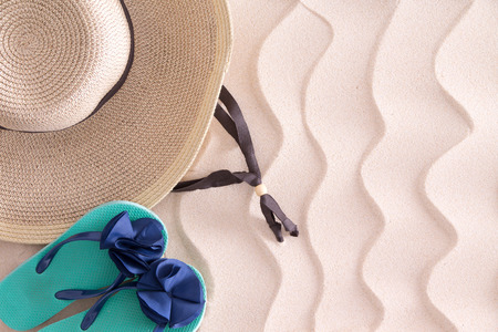 brim: Young girl gone swimming leaving her wide brimmed straw sunhat and slip slops on the golden beach sand with a decorative wavy pattern and copyspace, view from above