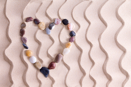 Decorative pebble heart of waterworn alluvial quartzite, agate and basalt stones symbolic of love and romance on golden beach sand with an ornamental pattern of wavy lines and copyspace