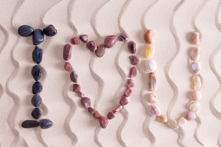 quartzite: I Love You romantic message in colorful pebbles on golden beach sand with a decorative pattern of undulating wavy lines using waterworn basalt, agate and quartzite found in nature on the seashore Stock Photo