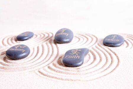 sand art: Zen art with swirling lines in golden sand surrounding smooth basalt rocks with symbols and text signifying peace, harmony, hope, belief, and serenity in ancient Japanese tradition