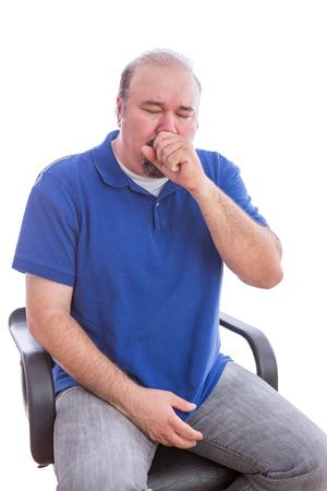 tosiendo: Cierre de Enfermos hombre barbudo en la camisa azul que se sienta en una silla individual que sufre de tos. Aislado en el fondo blanco. Foto de archivo