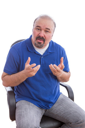 non verbal communication: Close up Bearded Middle Age Guy Sitting on a Chair, Explaining Something While Looking at the Camera. Isolated on White Background.