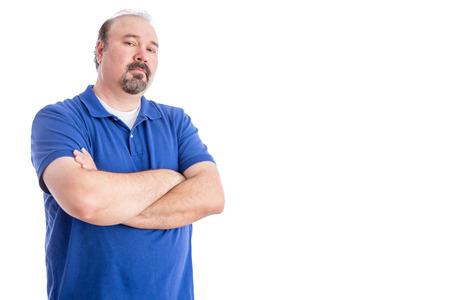 desconfianza: Confiado hombre de mediana en la camisa azul, cruzando los brazos sobre su estómago y mirando a la cámara agresivamente. Aislado en el fondo blanco con copia espacio a la derecha.