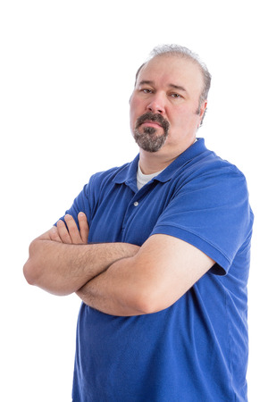 inscrutable: Portrait of a Serious Bearded Man in Blue Polo Shirt, Crossing his Arms and Looking at the Camera in an Aggressive Look. Isolated on White Background.