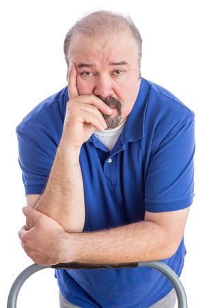 empatia: Close up pensativo adulto Hombre barbudo que se inclina contra el respaldo de una silla con la mano en su cara y mirando a la cámara. Aislado en blanco.