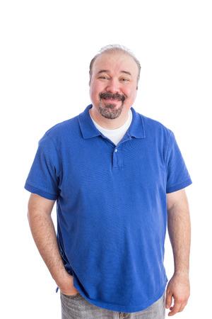 ブルーのポロシャツは、彼のポケットに 1 つの手、白背景に分離されたカメラでの笑顔で楽観的な成人男の肖像画。