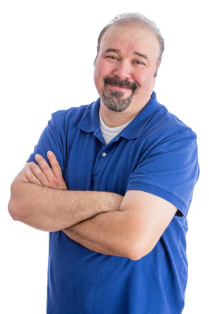 convivial: Close up Portrait of a Smiling Bearded Adult Guy in Blue Polo Shirt, Crossing his Arms over His Stomach While looking at the Camera. Isolated on White Background. Stock Photo