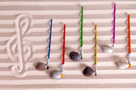 partition musique: Musique à la notion de bord de mer avec un arrangement artistique de notes de musique formé de cailloux et de pinceaux colorés sur un score de fond composé d'une alternance de lignes de sable doré Banque d'images