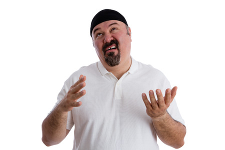 Man offering up a so-so prayer in an undecided frame of mind pulling a comical face as he looks to Heaven, isolated on white Stock Photo