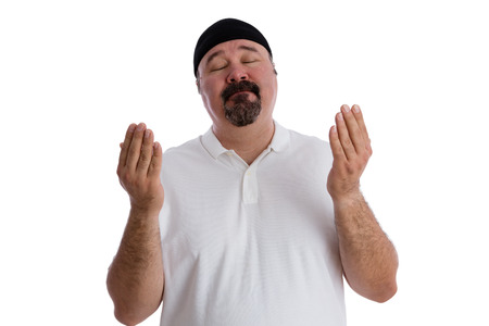 devout: Devout religious middle-aged man deep in prayer standing with is eyes closed and hands raised in supplication, isolated on white Stock Photo