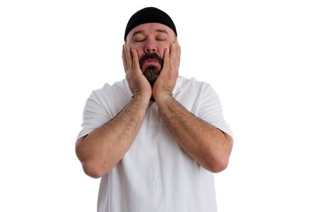 sinful: Sinful man seeking absolution praying to God with his hands to his cheeks, eyes closed and a devout expression as he seeks forgiveness, isolated on white