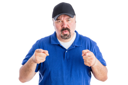 quizzical: Puzzled middle-aged man with a goatee wearing a baseball cap pointing at the camera with a quizzical frown as he seeks clarification, isolated on white