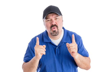 quizzical: Perplexed man pointing upwards with his fingers as he frowns at the camera with a puzzled quizzical expression requiring an explanation, isolated on white