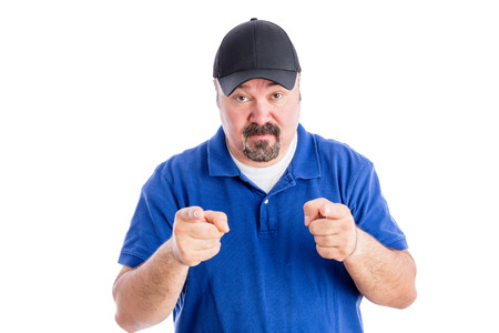 quizzical: Sceptical casual middle-aged man showing his disbelief pointing at the camera and raising his eyebrows in distrust, upper body isolated on white