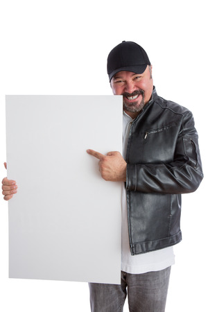 promotes: Charismatic trendy middle-aged man in a leather jacket and cap pointing to a blank white sign he is holding with a beaming smile as he promotes your product, isolated on white
