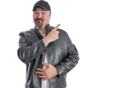 goatee: Jaunty trendy middle-aged man with a goatee wearing a grey leather jacket and cap pointing to blank copyspace for your advertising with a pleased expression, isolated on white