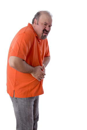 clutches: Middle-aged man with constipation grimacing in pain as he clutches his stomach in discomfit due to compaction of his feces and inability to enjoy a regular bowel movement