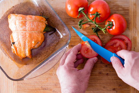 ovenbaked: Close up view from above of the hands of a male chef slicing tomatoes with a blue knife to accompany an oven-baked salmon steak fresh from the oven on a wooden counter