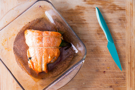 ovenbaked: Fresh oven-baked salmon fresh from the oven in a glass oven dish alongside a sharp blue kitchen knife on a wooden kitchen counter ready to be served, view from above