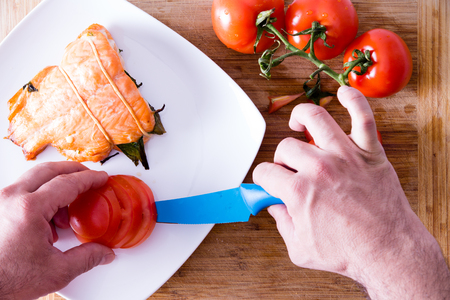 ovenbaked: Chef plating up a gourmet salmon dinner carefully arranging sliced fresh tomato alongside an oven-baked fish fillet, view from above