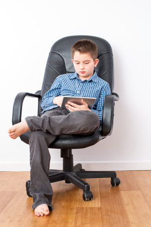 Busy Young Handsome Boy with Tablet Computer Sitting on a Black Office Chair with Legs Crossed and Bare Feet.