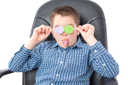 protruding eyes: Close up Funny White Boy in Checkered Shirt, Sitting on an Office Chair and Holding Lollipops Over his Two Eyes with Tongue Out. Isolated on White.