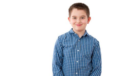 Retrato de un lindo 10 Year Old Boy con una dulce sonrisa dañosa, de pie contra el fondo blanco con espacio de copia. Foto de archivo