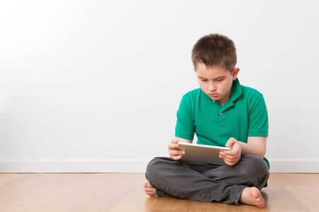 preteen boys: Serious Cute 10 Year Old Young Boy Sitting on the Floor with Legs Crossed, Busy with his Tablet Computer
