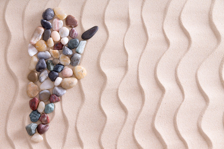 memento: Creative colorful pebble map of Argentina using smooth waterworn agate and quartzite stones on decorative beach sand with a wavy pattern depicting ripples, with copyspace for a travel template Stock Photo