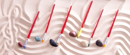 music staff: High Angle View of Music Staff with Treble Cleff Drawn Into Sand and Paintbrushes and Stones for Music Notes, Creating Music on Beach with Nature and Artistic Inspiration