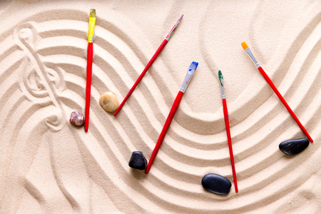 musical score: Harmony and music at the beach with an artistic conceptual image of a wavy score drawn in golden sand with a treble clef and musical notes of smooth pebbles and kids paintbrushes