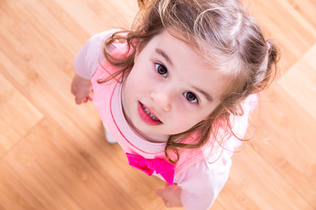 Pretty little girl with curly hair and beseeching eyes standing looking up into the camera as she asks for something that she wants, view looking down into her face with wood floor background