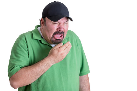 airborne: Upper Body Image of Overweight Man Wearing Green Shirt and Black Baseball Cap Covering Mouth While Sneezing in front of White Background Stock Photo