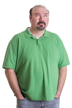 Portrait of Overweight Man Wearing Green Shirt Standing with Hands in Pockets and Looking Up Thoughtfully on White Studio Background photo
