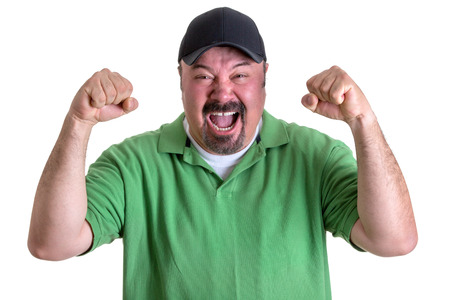 verbal: Close up Aggressive Bearded Middle Aged Man in Casual Green Polo Shirt and Black Cap, Yelling Out Loud with Fists Raised. Isolated on White Background.