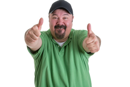 adherent: Portrait of Overweight Man with Goatee Wearing Green Shirt and Black Baseball Cap Smiling and Giving Thumbs Up Hand Gesture Toward Camera, on White Background