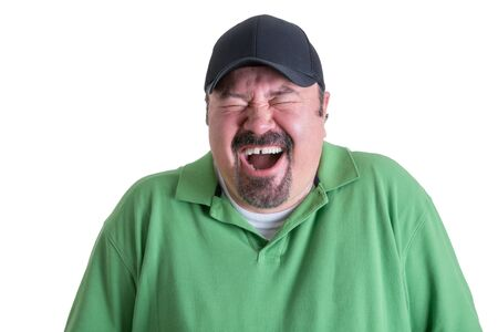Portrait of Overweight Man Wearing Green Shirt and Black Baseball Cap Laughing Ecstatically in front of White Background, Head and Shoulders Portrait of Joyful Man