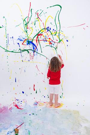 ragazze a piedi nudi: Figura intera Shot di una giovane Piccolo bambino, dipinto qualcosa di astratto su bianco Big Wall utilizzando colori diversi. Archivio Fotografico