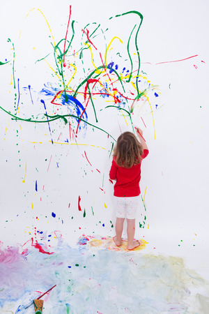 Full Length Shot of a Young Little Kid Painting Something Abstract on White Big Wall Using Different Colors.