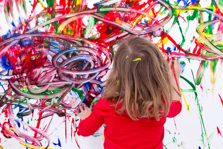 Close up Young Blond Kid Painting Abstract Design Using Various Colors on White Wall During her Painting Time.