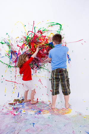 chromatic colour: Two Siblings Painting Contemporary Art on White Big Wall Using Colorful Paints During their Bonding Time. Stock Photo