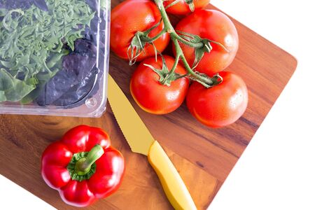 paring: Healthy fresh salad ingredients on a chopping board with a sharp paring knife with three varieties of lettuve in a punnet and vine tomatoes with red bell pepper alongside, isolated on white