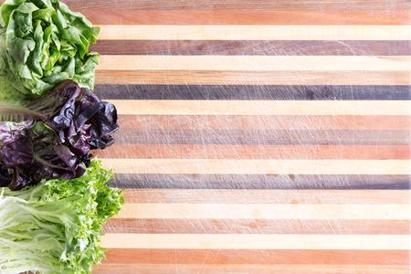 marqueteria: Frontera lechuga fresca con tres cultivares en una tabla de cortar de madera laminada decorativa con colores variados de la madera en un patrón de rayas paralelas, con copia espacio, visto desde arriba Foto de archivo