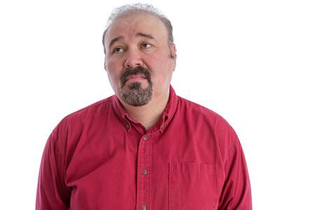 cabizbajo: Hombre de mediana edad con la calvicie y barba de chivo que llevaba una camisa de color rojo oscuro mientras mira hacia arriba a la izquierda con una expresión facial triste y deprimido, aislado retrato en blanco Foto de archivo