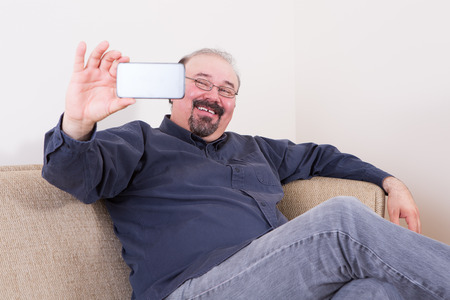beaming: Happy man taking a selfie for his friends on the social media on his smartphone posing on a couch at home looking at the camera with a beaming smile Stock Photo