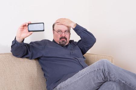 Homme vain de prendre un selfie sur son smartphone vérifier ses cheveux avec sa main comme il porte un regard critique sur l'écran tout en étant assis sur un canapé confortable à la maison Banque d'images