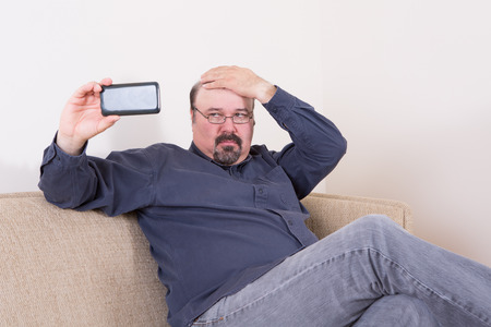 appraising: Vain man taking a selfie on his smartphone checking his hair with his hand as he looks critically at the screen while seated on a comfortable sofa at home Stock Photo