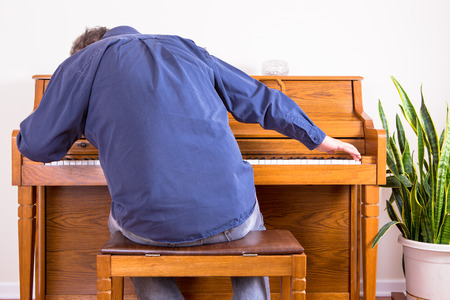 gusto: Enthusiastic man playing the piano with gusto stretching to either end of the keyboard, view from behind of him sitting on the stool leaning forwards Stock Photo