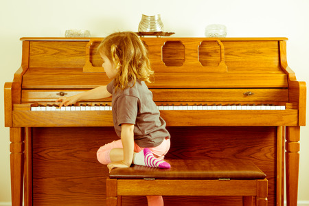 upright piano: Right note requires effort outside your comfort zone in a conceptual image with a little girl climbing on the stool to stretch across a piano keyboard for the correct key or note